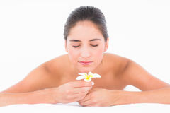 Un ritratto sorridendo abbastanza castana sulla tavola di massaggio con i fiori Fotografia Stock