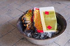 Un ritual para quemar el papel de oro al antepasado para pagar respecto y para celebrar Año Nuevo chino Imagen de archivo