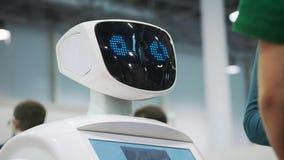 Un robot blanco obra recíprocamente con un colegial en una exposición de nuevas tecnologías El niño consigue conocido con