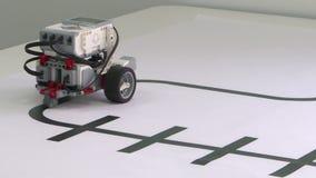 Un robot con tres paseos de las ruedas en una tabla blanca Robusteza elegante metrajes