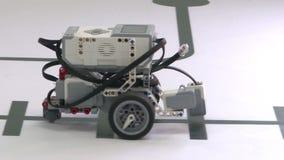 Un robot con tres paseos de las ruedas en una tabla blanca Robusteza elegante almacen de metraje de vídeo