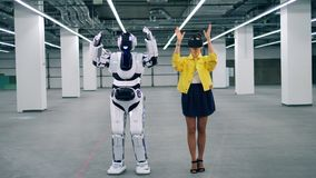 Un robot copie les mouvements de femme, alors qu'elle porte des lunettes de VR clips vidéos