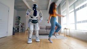 Un robot danse tandis qu'une femme saute dans une chambre Cyborg et concept humain banque de vidéos