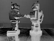 Un robot di due annate stringe le mani di legno su una m. solarized vecchio pavimento Fotografia Stock
