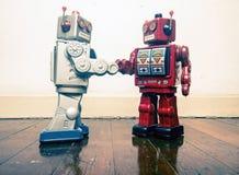 Un robot di due annate stringe le mani su un vecchio pavimento di legno Fotografie Stock
