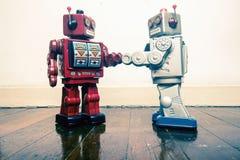 Un robot di due annate stringe le mani su un vecchio pavimento di legno Fotografie Stock Libere da Diritti
