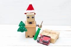 Un robot en un sombrero de santa sostiene un juguete del árbol de navidad y del screwdr Imagen de archivo libre de regalías