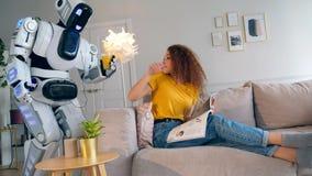 Un robot está trayendo un vidrio de jugo a una mujer joven almacen de metraje de vídeo