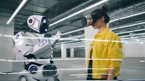 Un robot et une dame en VR-verres touchent des mains banque de vidéos