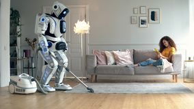 Un robot fait le nettoyage de vide tandis qu'une fille se trouvant sur un divan Cyborg et concept humain banque de vidéos
