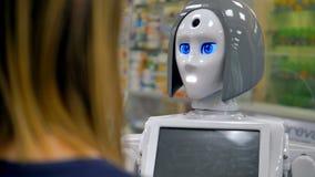 Un robot habla con un comprador femenino almacen de metraje de vídeo