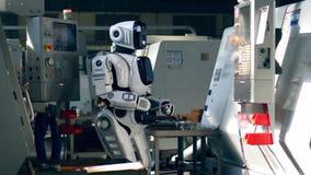 Un robot mecanografía en una tableta mientras que trabaja con las máquinas de la fábrica almacen de metraje de vídeo