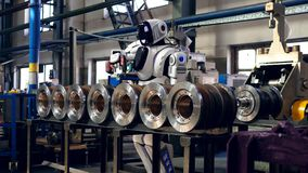 Un robot utiliza el destornillador eléctrico mientras que trabaja en una fábrica metrajes