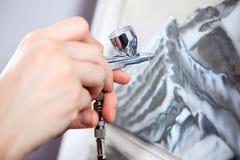Un rociador de la unidad o de la pintura del aerógrafo en el dibujo humano de la mano en la lona, opinión del primer Imagen de archivo