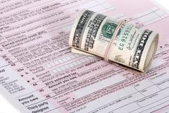 Un rodillo del dinero de los USD cerca de una forma de impuesto Fotografía de archivo libre de regalías