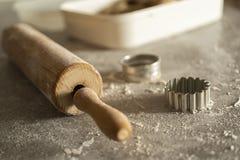Un rodillo y un equitment el cortar para cortar las galletas de la pasta de la galleta en una tabla de cocina con mucha harina fotografía de archivo libre de regalías