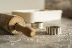 Un rodillo y un equitment el cortar para cortar las galletas de la pasta de la galleta en una tabla de cocina con mucha harina foto de archivo libre de regalías