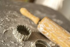 Un rodillo y un equitment el cortar para cortar las galletas de la pasta de la galleta en una tabla de cocina con mucha harina foto de archivo