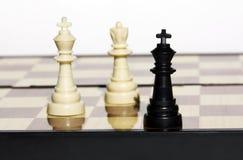 Un roi noir contre le roi blanc et une reine images stock