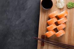 Un rollo clásico de Philadelphia con la salsa del wasabi, del jengibre y de soja en un tablero de madera Salmones, queso de Phila Foto de archivo libre de regalías