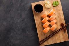 Un rollo clásico de Philadelphia con la salsa del wasabi, del jengibre y de soja en un tablero de madera Salmones, queso de Phila Imagenes de archivo