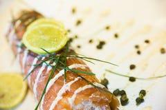 Un rollo de color salmón con la salsa Imagen de archivo