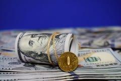 Un rollo de dólares y una moneda de 10 rublos rusas en el fondo de dispersado cientos billetes de dólar foto de archivo libre de regalías