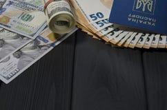 Un rollo grueso de las viejas cuentas del ciento-dólar atadas con una goma roja miente al lado del pasaporte biométrico de un ciu imagenes de archivo