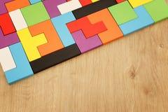 Un rompecabezas cuadrado colorido del rompecabezas chino, sobre la tabla de madera imágenes de archivo libres de regalías