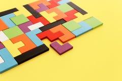 Un rompecabezas cuadrado colorido del rompecabezas chino, sobre la tabla de madera imagenes de archivo