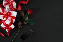 Un rose et boîte-cadeau rouge foncé avec le ruban rouge sur le backgrou noir Photographie stock libre de droits