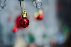 Un rosso Bobble l'ornamento di Natale che pende da un cavo Fotografie Stock Libere da Diritti