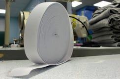 Un rotolo del nastro di gomma elastico sul tricottare produzione Immagini Stock