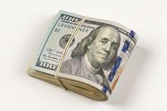 un rotolo di 100 banconote in dollari isolato su fondo bianco Fotografia Stock Libera da Diritti