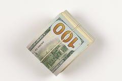 un rotolo di 100 banconote in dollari su fondo bianco Fotografia Stock
