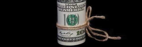 Un rotolo di cento banconote in dollari legate con una corda su un fondo nero È individuato verticalmente Vista laterale fotografia stock libera da diritti