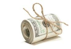Un rotolo di cento banconote in dollari legate nella corda della tela da imballaggio su bianco Immagine Stock