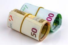Un rotolo di cento euro e di cinquanta banconote Fotografia Stock