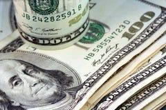 Un rotolo di venti fatture del dollaro sulle centinaia Fotografia Stock