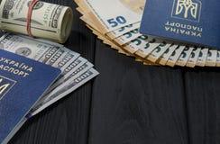 Un rotolo spesso di vecchie cento banconote in dollari legate con un elastico rosso si trova accanto ai passaporti biometrici dei immagini stock