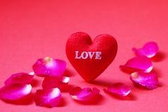 Un rouge en forme de coeur avec l'amour et les pétales de rose sur le fond rouge Image libre de droits