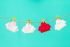 Un rouge parmi la pose de papier peint blanche de chemise d'origami avec l'icône o de visage Images stock
