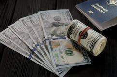 Un rouleau épais de vieux cent billets de banque du dollar a attaché une bande élastique rouge se trouve sur le favori de nouveau photo libre de droits