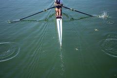 Un rowing de la chica joven en barco Imagenes de archivo