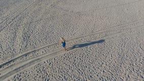 Un rubio en un vestido azul corre a lo largo de la arena amarilla de una playa del mar Báltico temprano por la mañana Sombras lar almacen de video