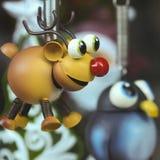 Un Rudolph el ornamento sospechado rojo del reno con un pingüino Imagen de archivo libre de regalías