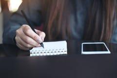 Un ` s de femme remet l'écriture sur le carnet avec le téléphone portable sur la table photos libres de droits