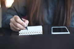 Un ` s de la mujer da la escritura en el cuaderno con el teléfono móvil en la tabla fotos de archivo libres de regalías