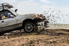 Un ` s de voiture emballant dans la boue pendant une concurrence de emballage tous terrains Photographie stock libre de droits