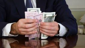 Un ` s del hombre de negocios da la cuenta de cientos billetes de dólar en una tabla almacen de video